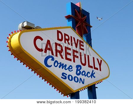 Drive Carefully Come Back Soon Sign in Las Vegas with Departing Airplane