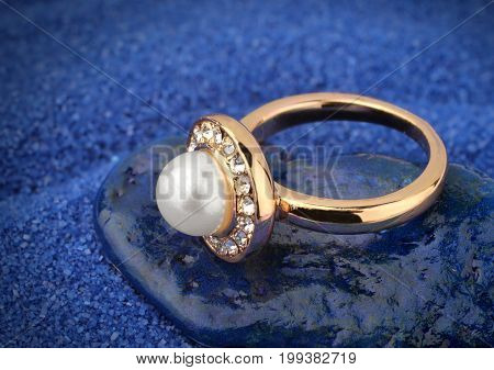 Jewelery ring with pearl on blue background