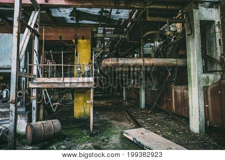 Abandoned industrial interior of abandoned factory with equipment, toned