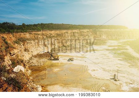 Open cast Quarry with heavy duty machinery equipment in sunlight, copy space
