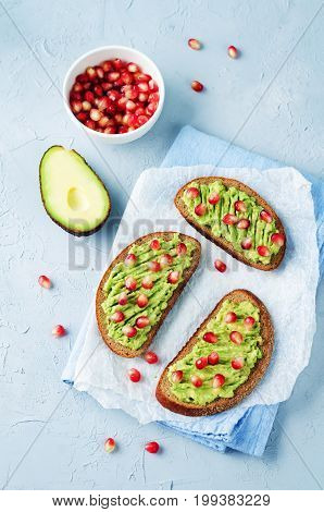 Smashed avocado pomegranate rye sandwiches on a stone background