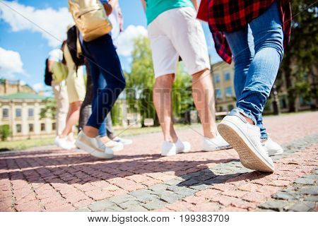 Cropped Close Up Low Angle Photo Shot Of Six Student`s Legs, Walking On The Cobbles. Sunny Spring Da