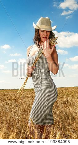 Pretty woman close up portrait. in hat in the wheat field on blue sky background