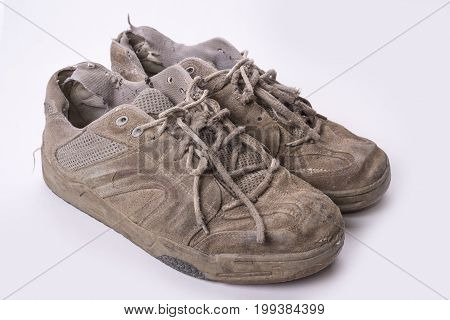 Pair of old wear out sneakes on white background