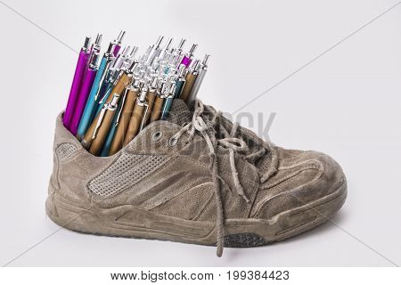 Stack of pens inserted to the old wear out sneaker