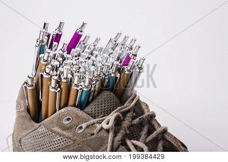 Old wear out sneaker is used like a pen holder
