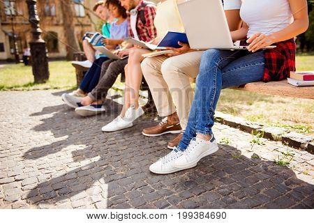Cropped close up low angle photo shot of six student`s legs sitting outside on a sunny spring day students are preparing for tests together