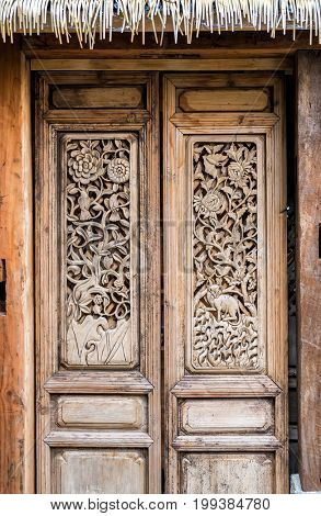 Old style wooden Chinese doors decorated by traditional carved wood with latch