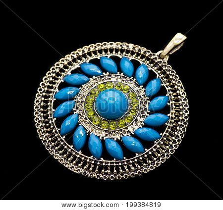 blue pendant with gems on black background