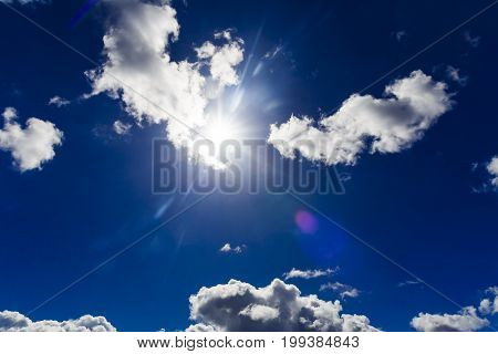 Dramatic Sun Flare With Fluffy Clouds Into Deep Blue Sky, High Contrast Editing