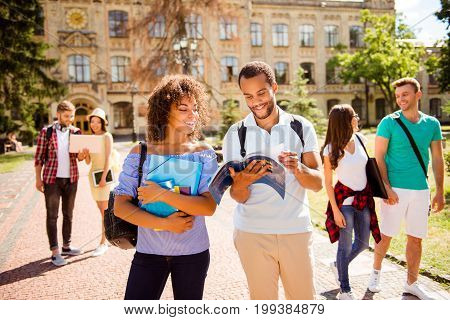 Couples of international students are walking after studies holding hands chatting smile enjoying helping each other with studies. All dressed in comfortsble casual wear sunny spring day