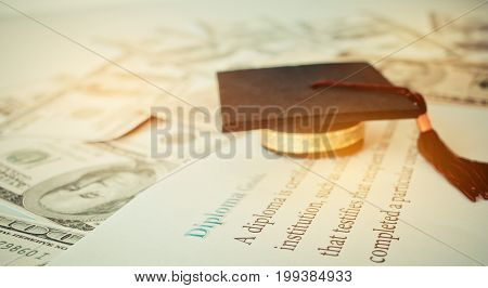 Graduation cap on a letter book Diploma Goals Concept of graduate education abroad in university requires a lot foreign currency Dollars to bring success in famous institution.