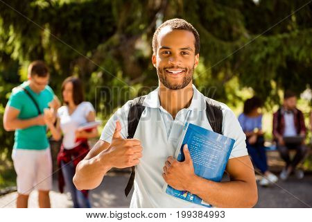 Young cheerful successful african nerdy student is showing thumb up standing with book his classmates on the background park near campus sunny day