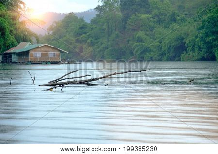 Rain On Stump In The River And Houseboat At Kwai River Landscape In Kanchanaburi, Thailand. Natural