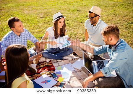 Close up cropped photo of group of diverse cheerful students studying outdoors sitting on a plaid on the grass in comfortable outfits hats smiling enjoying