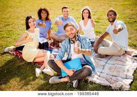 It`s more easy together! Six cheerful classmates are sitting on plaid on the green grass in spring sunny park near campus and gesturing like signs so happy and cheerful
