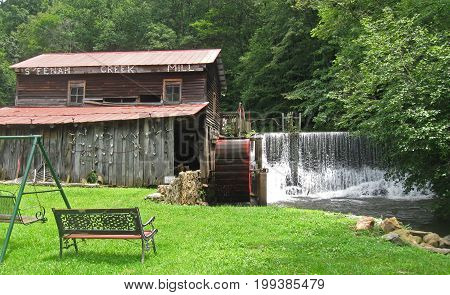 water pours over a dam next to a gristmill, a bench and swing in the foreground