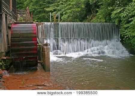 slow shutter shot of water pouring over a dam at a gristmill