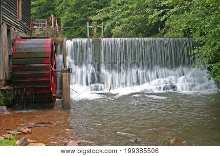 Slow shutter speed shot of water pouring over a dam at a gristmill