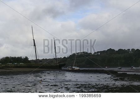 Cornish river estuary with old ship moored beside quay
