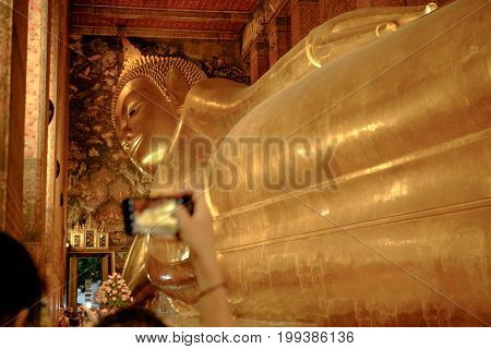 The Big Golden Reclining Buddha And Blurred Tourist Taking Photo By Mobile, Within Wat Pho Temple Is