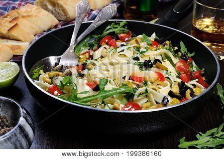 Pasta with crushed olives and cherry tomatoes arugula. Horizontal shot.