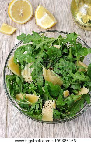 Arugula (rocket) salad dressed with balsamic soy sauce Parmesan shavings and freshly ground black pepper sesame.