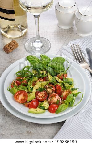 Delicate slices of avocado with tomatoes dressed pesto sauce.
