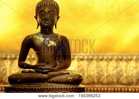 Buddha statue of meditation pose in peaceful atmosphere. Golden background is part of huge reclining Buddha statue in a famous temple in Bangkok Thailand and popular tourist place.