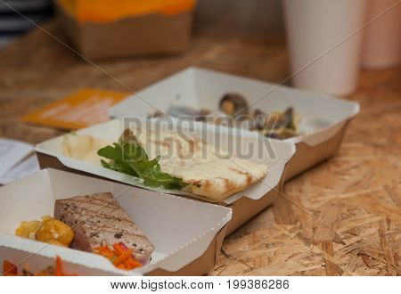 little fish snacks in cardboard boxes in the street cafe
