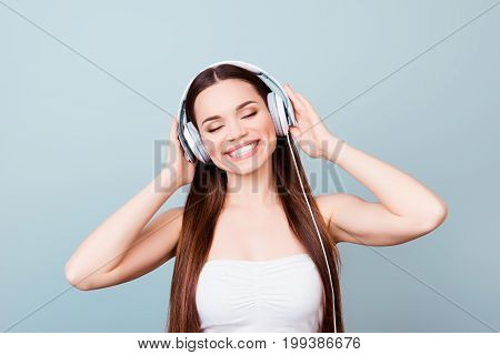 Charming Young Girl With Toothy Smile In Modern Headphones. She Is Dreamy And Happy, Listening To He
