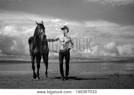 Macho Man Handsome Cowboy And Horse On The Background Of Sky And Water.