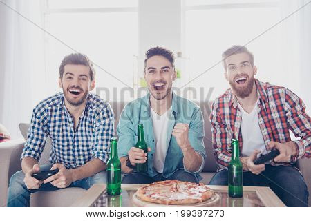 We are the champions! Bachelor men`s life. Three happy joyful men are sitting on sofa and playing video games indoors at home with beer and pizza smiling gesturing enjoying