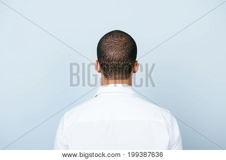 Rear View Of An American Muklatto Guy, In Smart White Formal Shirt, Standing On A Pure Blue Backgrou