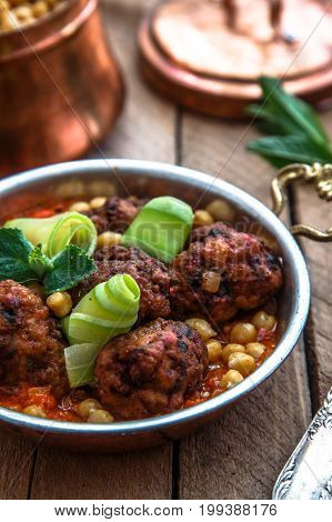 roasted lamb kofte with tomato sauce in copper pan, close view.