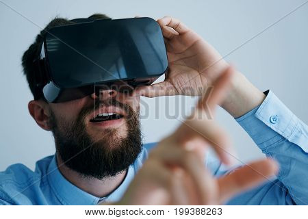 A man with a beard plays on a light background in glasses of virtual reality, entertainment.