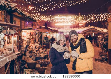 Beautiful Young Couple Outdoors At Winter On A New Year`s Eve With Hot Drinks, Having Fun At A Winte