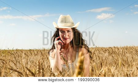 Pretty woman close up portrait. in hat in the wheat field on blue sky background.