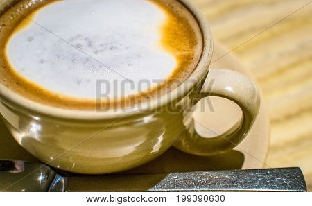 Latte with frothy foam tan mug side view