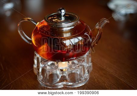 Glass infuser teapot with tea on the trivet