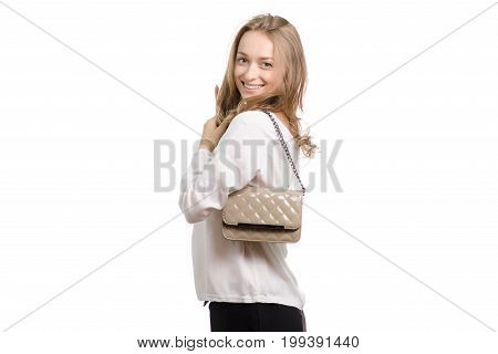 Beautiful girl with a lacquer bag on her shoulder on a white background isolation