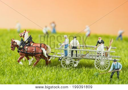 An agricultural photo of working toy farmers and a cart with dobbins.