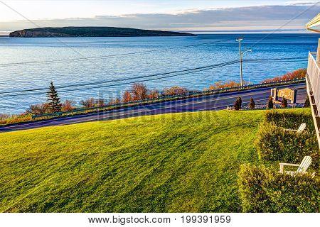 Perce Canada - June 7 2017: Bonaventure Island during sunrise in Gaspe Peninsula Quebec Canada Gaspesie region with blue water and hotel sign