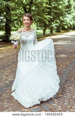 Front view of bride holding wedding bouquet. Bride walking with a wedding bouquet in the summer park. Woman with a bouquet. Toned