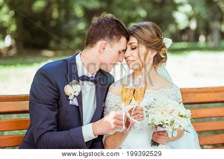 Close up portrait of groom and bride sits on the bench in the park. Groom and bride with champagne glasses outdoor. Loving wedding couple. Toned