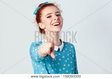 Funny redhead girl in light blue dress having pointing finger at camera and toothy smile focus on her face. Isolated studio shot on gray background