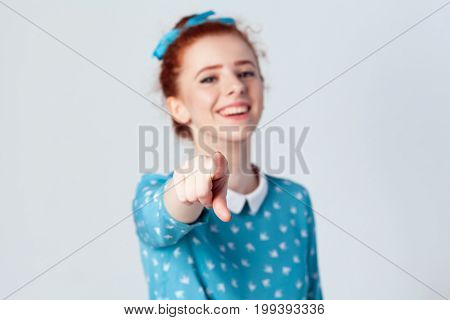 Funny ginger girl in light-blue dress having pointing finger at camera and toothy smile focus on her finger. Isolated studio shot on gray background