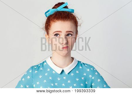 Indoor isolated studio shot on gray background of cute ginger girl looking away having doubtful and indecisive face expression pursuing her lips. Confused young woman posing isolated at light gray wall