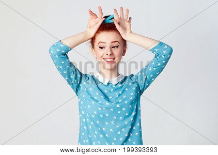 Stunning redhead girl with fabulous smile wearing blue dress holding hands on head pretending to be bunny. Isolated studio shot on gray background.