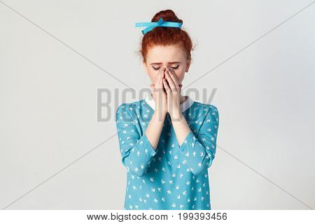 Portrait of unhappy depressed and crying young caucasian girl with ginger hair feeling ashamed or sick covering face with both hands keeping eyes closed. Human face expressions and emotions concept. Isolated studio shot on gray background.
